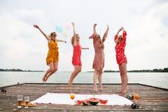 Quatre meilleurs amis riant et sautant au lac Images libres de droits