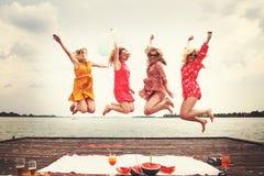 Quatre meilleurs amis riant et sautant au lac Photos stock