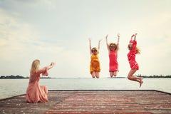 Quatre meilleurs amis riant et sautant au lac Image stock