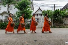Quatre moines bouddhistes rassemblent l'aumône dans Luang Prabang, Laos images stock