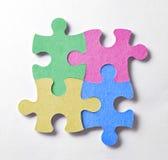 Quatre morceaux colorés de puzzle disposés dans une place et métallisés Photographie stock