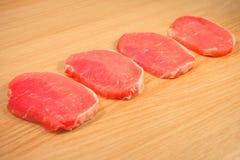 Quatre morceaux de viande de porc coupés en tranches sur un conseil en bois avec un conseil Photos stock