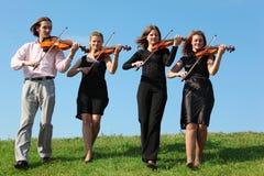 Quatre musiciens vont jouer des violons contre le ciel Photographie stock libre de droits