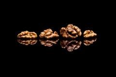 Quatre noix sur le fond réfléchi noir Photo stock