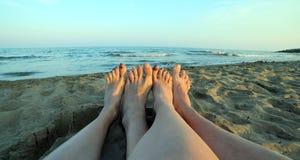 Quatre nu-pieds par un couple par la mer image libre de droits