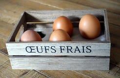 Quatre oeufs bruns dans une boîte en bois avec les mots français Photographie stock libre de droits