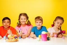 Quatre oeufs de pâques de couleur d'enfants à la table Images stock