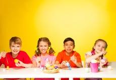 Quatre oeufs de pâques de peinture d'enfants à la table Photos libres de droits