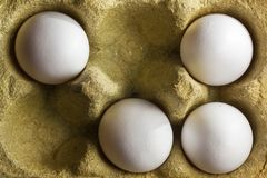 Quatre oeufs organiques dans une boîte faite en herbe Photos libres de droits