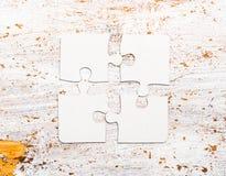 Quatre ont relié les morceaux blancs de puzzle sur la table Photographie stock libre de droits