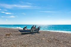 Quatre pêcheurs locaux non identifiés poussant leur bateau à la mer et se préparant à la pêche, chien les suivant Photographie stock libre de droits