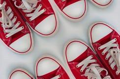 Quatre paires d'espadrilles rouges sur une surface en bois blanche Photographie stock