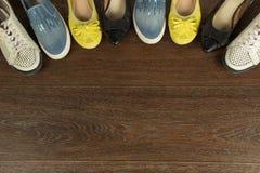 Quatre paires de chaussures du ` s de femmes de blanc, de jaune, de bleu et de noir dessus Photographie stock