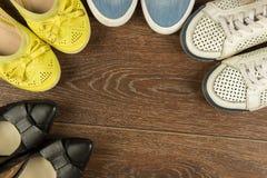 Quatre paires de chaussures du ` s de femmes de blanc, de jaune, de bleu et de noir dessus Images stock