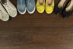 Quatre paires de chaussures du ` s de femmes de blanc, de jaune, de bleu et de noir dessus Photos stock