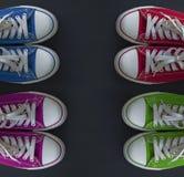 Quatre paires de la jeunesse colorée d'espadrilles sur une surface noire Photographie stock libre de droits