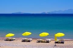 Quatre parapluies jaunes sur la plage en Grèce photo libre de droits