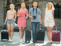 Quatre personnes de déplacement adultes marchant dans la ville Photographie stock