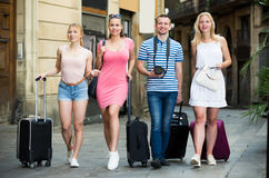 Quatre personnes de déplacement gaies marchant dans la ville Image libre de droits