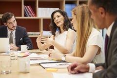 Quatre personnes lors d'une réunion de salle de réunion d'affaires image libre de droits