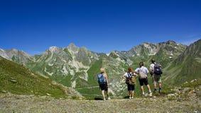 Quatre personnes observant autour sur une montagne Images libres de droits