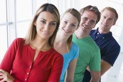 Quatre personnes restant dans le sourire de couloir Image libre de droits