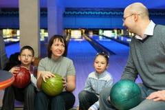 Quatre personnes s'asseyent communiquent dans le club de bowling Image libre de droits