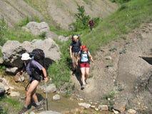 Quatre personnes sur le trekking d'été Photographie stock libre de droits