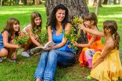 Quatre petites filles donnant la maman fleurit en parc photo libre de droits