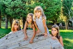 Quatre petites filles jouant en parc images stock