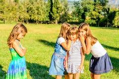Quatre petites filles jouant ensemble et secrets de chuchotement image stock