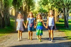 Quatre petites filles marchant par le parc Photos libres de droits