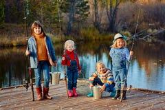Quatre petites filles pêchent des poissons sur un ponton en bois Week-end au lac Pêche avec des amis Photos libres de droits
