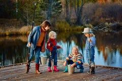 Quatre petites filles pêchent des poissons sur un ponton en bois Week-end au Th Photos stock