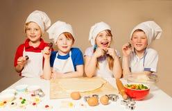 Quatre petits chefs heureux jouant des boulangers Photo libre de droits