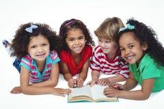 Quatre petits enfants lisant un livre ensemble Photographie stock libre de droits