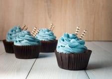 Quatre petits gâteaux avec de la crème bleue en papier brun forment photographie stock