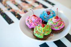 Quatre petits gâteaux lumineux colorés avec de la crème et mensonge d'arrosage sur un plateau Photos libres de droits