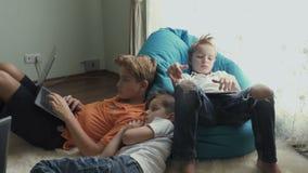 Quatre petits garçons passent le temps libre à la maison avec les instruments électroniques banque de vidéos