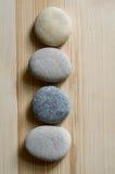 Quatre pierres sont alignées dans une ligne sur le fond en bois clair Images stock