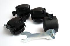 Quatre plus petites roues de roulette avec un outil fixe assorti de clé d'installation pour une table de travail images libres de droits