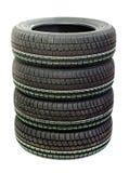 Quatre pneus neufs empilés sur le fond blanc Images libres de droits