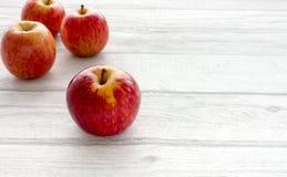 Quatre pommes rouges entières sur Grey Wooden Background image stock