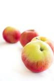 Quatre pommes rouges sur le fond blanc Image libre de droits