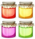 Quatre pots colorés qui sont étroitement couverts Photo libre de droits