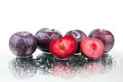 Quatre prunes mûres pourpres et une prune cutted sur le fond blanc de miroir d'isolement étroitement vers le haut du macro dans l photo stock