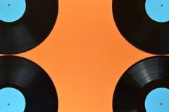 Quatre quarts de disque vinyle noir sur l'orange Photo stock