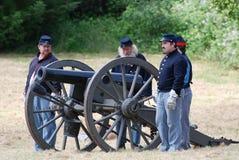 Quatre reenactors se tenant prêt un canon de guerre civile Photographie stock