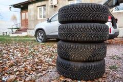Quatre roues de pneu d'hiver prêtes pour changer près de la voiture, copyspace Images libres de droits