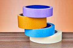 Quatre rouleaux multicolores de bande écossaise ont plié la pile sur la table Images stock